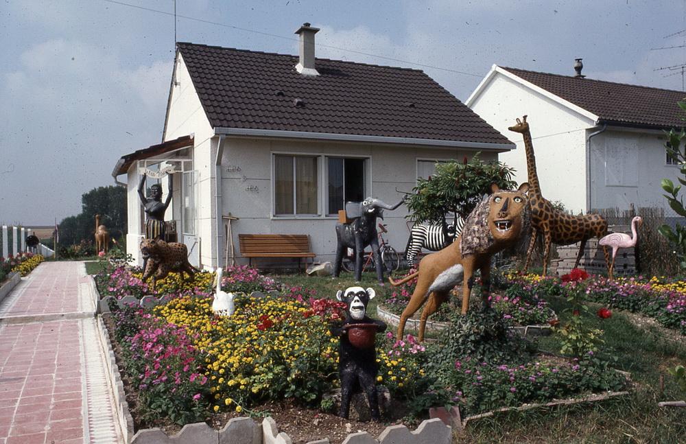 La « Petite Afrique » de Jules Damloup,1/1 Ayant pris sa retraite de cultivateur en 1969, Jules Damloup (1898-1985) peut enfin réaliser son rêve : sculpter dans le ciment et installer dans son jardin tous les animaux cette Afrique qu'il imagine ! Lions, singes, éléphants, girafes, oiseaux multicolores, zébres et flamands roses grandeur nature sont réunis sous le regard de la gardienne des lieux vêtue d'un léger costume réalisé à partir d'un rideau de cuisine et qui accueille les curieux, tous attirés par cette maison au jardin singulier et exotique des environs de Pithiviers.  Boësses, Loiret, 45390.