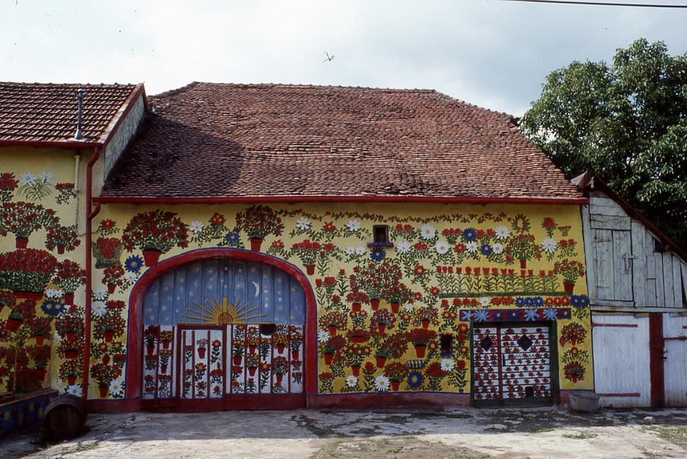 La maison de fleurs d'Eugène Juif, 1/2 C'est dans la petite commune de Vy-lès-Lure, qu'Eugène Juif (1867- ?) et son épouse Caroline habitent une maison le long de la route départementale. Eugène est un ancien ouvrier forestier et tout son temps libre a été occupé par la décoration peinte de sa maison, au sens le plus large du terme. En effet, murs des façades, fenêtres, portail, mais aussi murs de l'intérieur, objets et même la carrosserie de son cabriolet ! Les grandes et belles fleurs rouges ou blanches en pot rouge qui parsèment toute la façade peinte d'un jaune vif transforment l'ensemble en un monument de gaité et de lumière et éclairent le sourire se Caroline et Eugène qui, volontiers, accueillent les visiteurs et se prêtent avec plaisir au jeu des photographies !  Vy-lès-Lure, Haute-Saône, 70200.