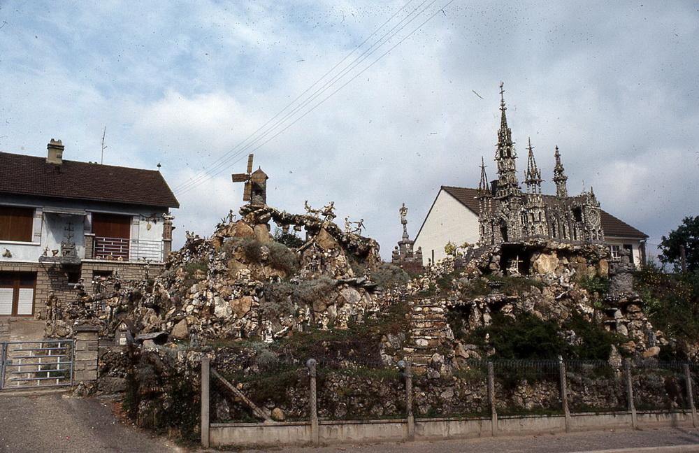 Le monde de cailloux de Marcel Landreau 1/3 C'est en 1961 que Marcel Landreau (1922-1992) acheta un terrain à Mantes-la-Jolie pour y construire sa maison. Très vite, celle-ci fut peuplée de personnages construits à partir d'assemblages de pierres trouvées puis, une cathédrale monumentale fut construite de laquelle sortait en musique une grande procession de mariage. Des centaines de personnages à l'incroyable expressivité peuplaient son jardin, faits uniquement des dizaines de milliers de cailloux ramassés aux alentours. Les scènes de genre se multiplièrent, les références à des faits ou à des personnages réels racontaient toujours plus d'histoires et le talus de son jardin se transforma en une véritable encyclopédie à l'imaginaire humoristique et extraordinaire. Mais Marcel Landreau dut quitter sa maison en 1989 et se résigna à déplacer un grand nombre de ses sculptures dans une autre maison à Thouars dans les Deux-Sèvres. Un grand nombre a pu être sauvé après sa mort et certaines se trouvent à présent conservées au Musée de l'Art Brut de Lausanne ou à La Fabuloserie en Bourgogne. Mantes-la-Ville, Yvelines, 78711.