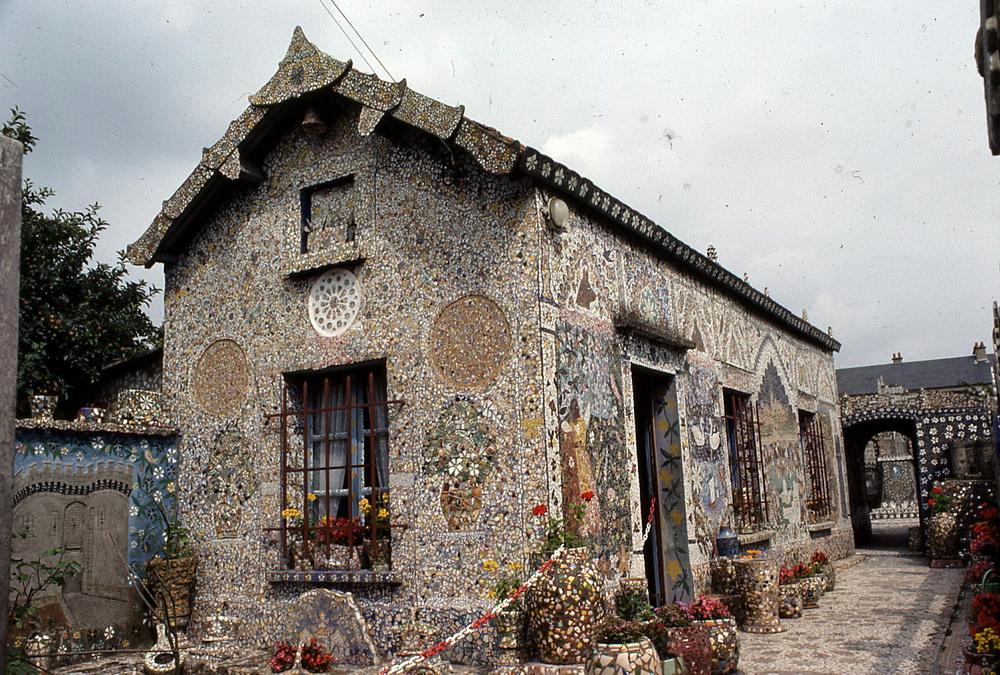 La maison féérique de Raymond Isidore 1/6 C'est pendant une trentaine d'années, de 1930 jusqu'à la fin de sa vie, que Raymond Isidore (1900-1964) a consacré tout son temps de libre à embellir sa maison puis son jardin. Avec son épouse, Adrienne, il achète un petit terrain sur lequel il entreprend la construction d'une maison de ses propres mains. Deux années plus tard, la maison terminée, c'est la décoration qu'il attaque en utilisant des morceaux d'assiettes et de faïence cassés qu'il trouve au rebut. Intérieur, objets usuels, mobilier, murs extérieurs, sols et plafonds, tout sera recouvert pour transformer le lieu de vie du couple et de leurs enfants en un environnement total ou l'art, la beauté des matériaux simples et les histoires occupent l'intégralité de l'espace et de l'esprit. Reconnu par quelques artistes dès 1952, il reçoit la visite de Picasso et Robert Doisneau le photographie. Raymond Isidore est décédé en 1964 et, en 1977, sa femme Adrienne, décédée en 1986, occupait toujours la maison. La Ville de Chartres a acquis la Maison en 1981 et l'a faite classée Monument historique.  Chartres, Eure-et-Loir, 28000.
