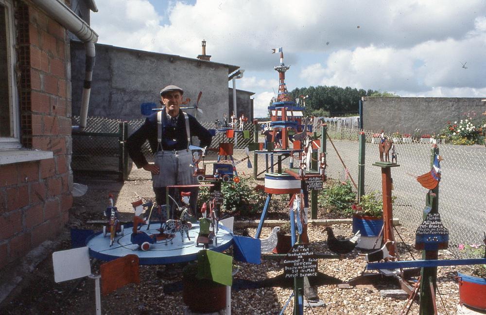 Le jardin en trois couleurs de Robert Pichot 1/3 C'est au sud de la ville du Mans, à La Suze-sur-Sarthe, que Robert Pichot a installé ses petites sculptures dans son jardin. Une particularité : elles ne sont peintes que de trois couleurs, bleu, blanc et rouge ! Si scènes et personnages militaires sont représentés, une tour porte-drapeau, un taxi hélicoptère, des manèges ou des coqs et poules emplissent le petit espace de son jardin et la première sensation qu'il donne est plutôt festive que militaire. Situé le long de la route de Malicorne, c'est délibérément aux passant que les installations s'adressent, complétées par des panneaux qui expliquent clairement les intentions de leur auteur qui, on doit bien le dire, n'en est pas peu fier !  La Suze-sur-Sarthe, Sarthe, 72210.